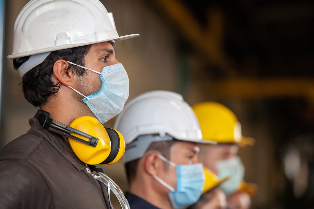 Field workers wear protective face masks for safety on a construction project