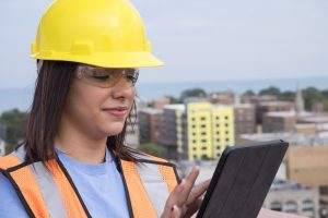 Female contractor at a work site using Premier Construction Software on ipad/tablet