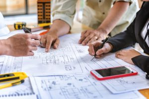 project management team checks construction blueprints on new project with engineering tools at desk in office.