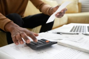 Construction business owner calculating receipts for cost plus billing