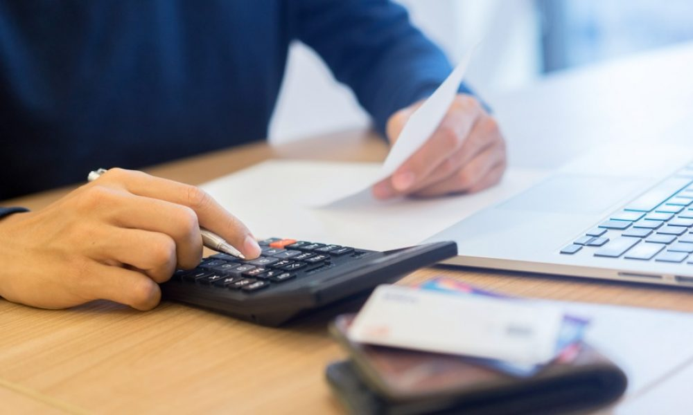 construction business owner calculating payroll for field workers