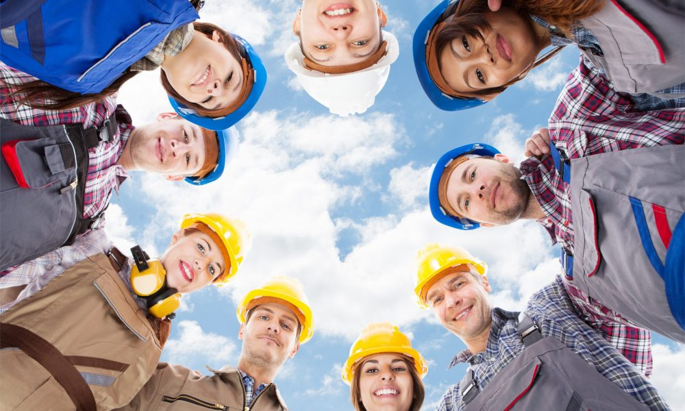 Directly,Below,Portrait,Of,Multiethnic,Architects,Standing,In,Huddle,Against
